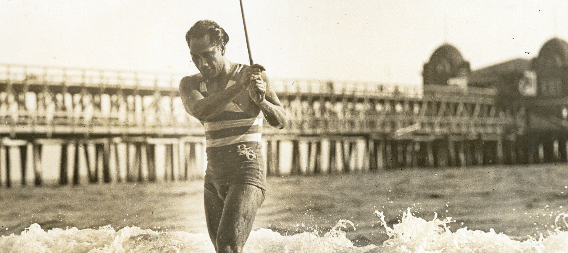 Duke exiting the ocean with stick in hand