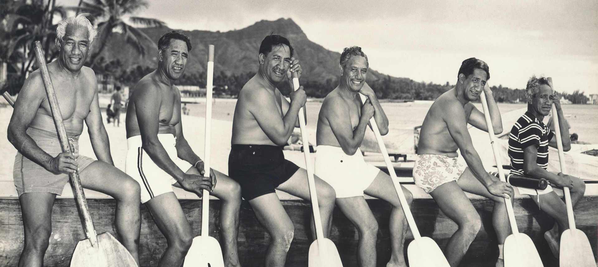 Duke and men sitting lined up by the shore with oars