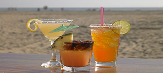 Three cocktails with the beach in the background