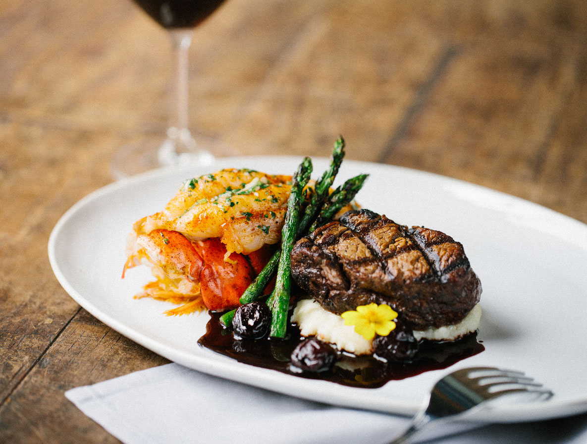 photo of a steak and seafood dinner with a glass of wine